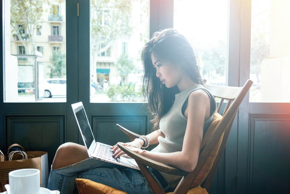 girl blogging laptop window