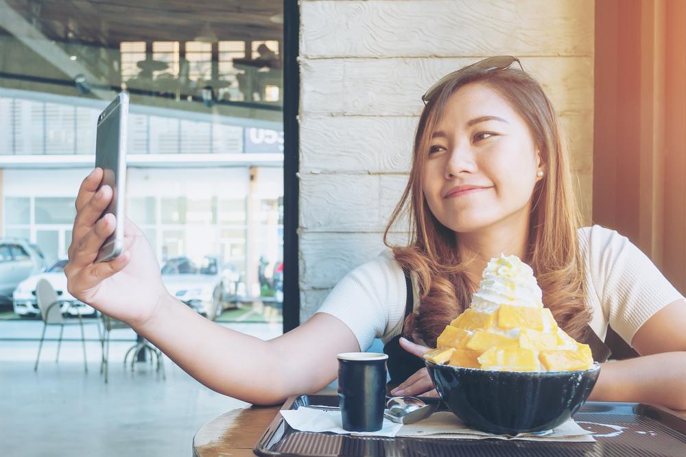 An asian woman using smart phone before eat Bingsu