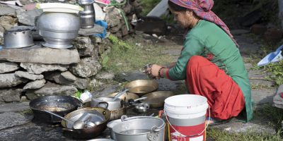 woman cleaning utensils outdoor india