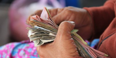 A woman holding and counting a stack of cash