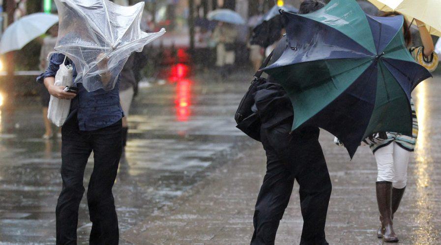 japan typhoon people umbrellas