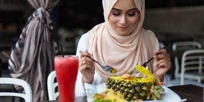malay woman eating at cafe with juices and food