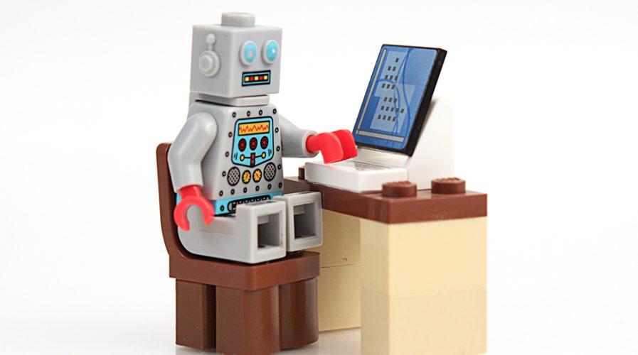 Studio shot of stack of Lego robot at computer