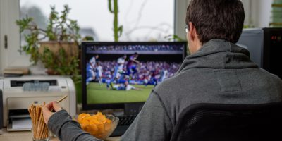 male gamer playing football game on computer