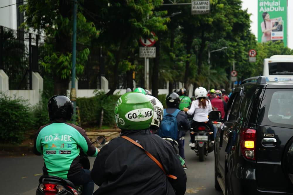 a gojek rider taking passengers in indonesia