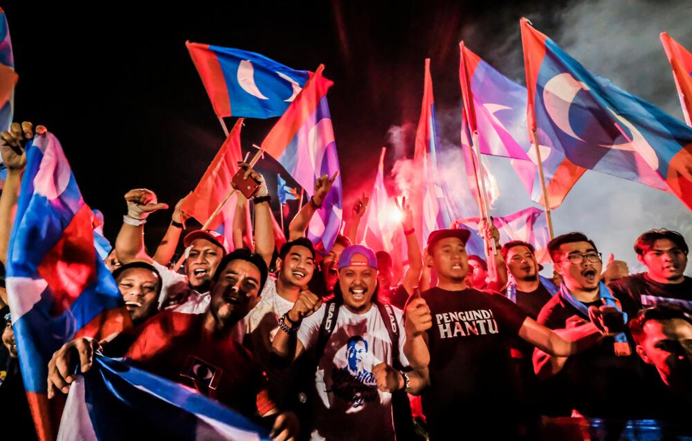 supporters waving flags celebrating the win of pakatan harapan
