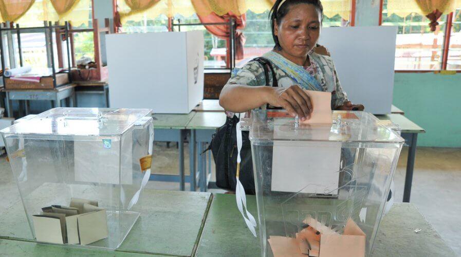a woman casting a ballot into the ballot box
