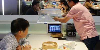 A man getting food from a robot at the ROBOT.HE restaurant in Shanghai.
