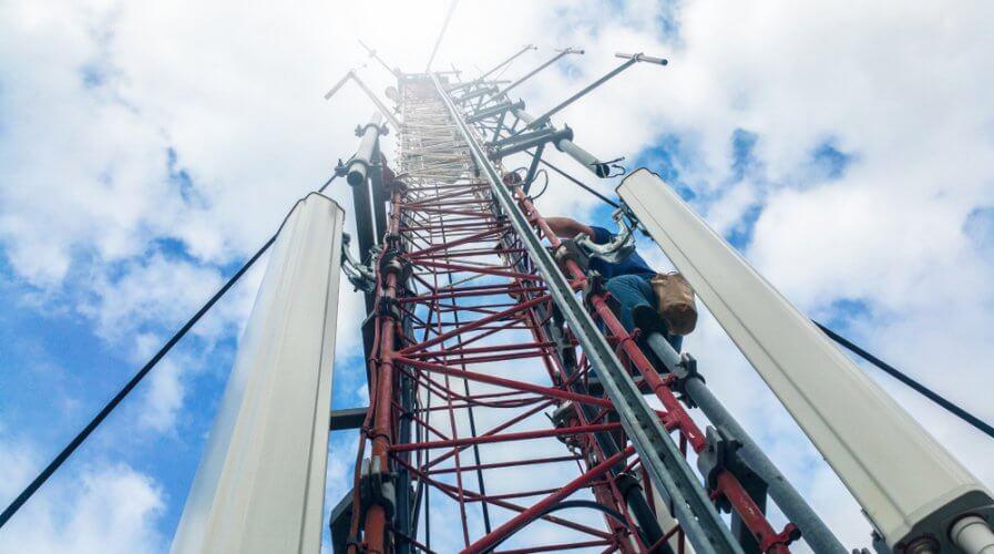 a worker climbing up a communications tower