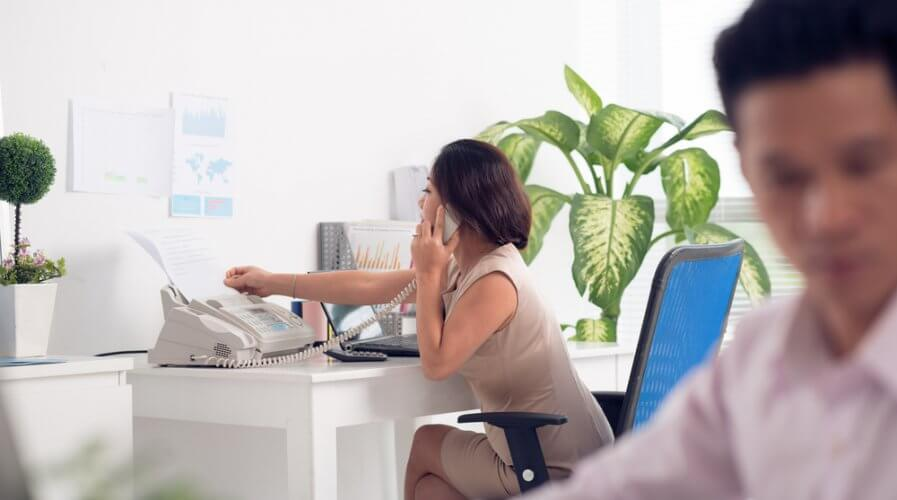 a woman receiving fax while on the phone