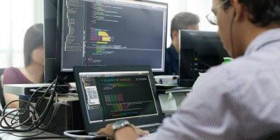 a software developer writing code on a screen