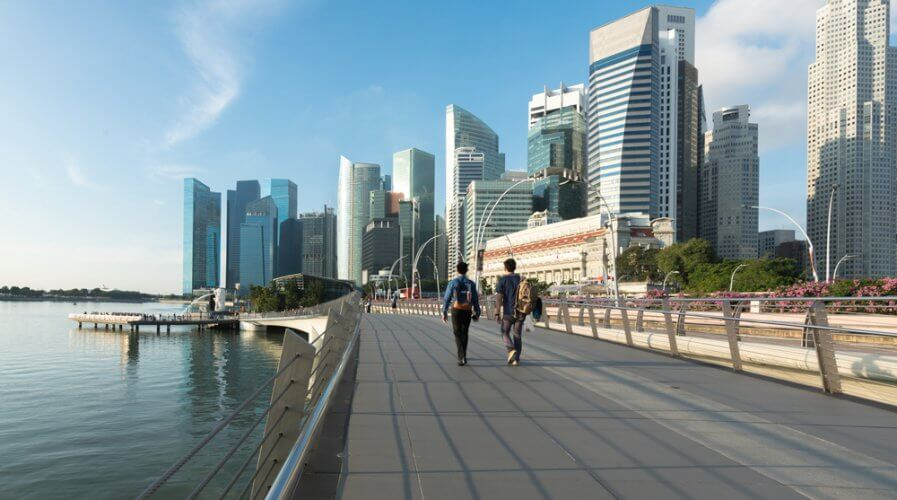 people walking with the backdrop of singapore's financial district