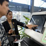 An airport staff member shows a passenger how to register his personal details at a facial recognition counter. Source: AFP