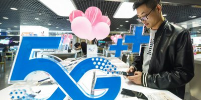 A customer looks at a mobile phone next to a 5G logo at a store in Hangzhou in China