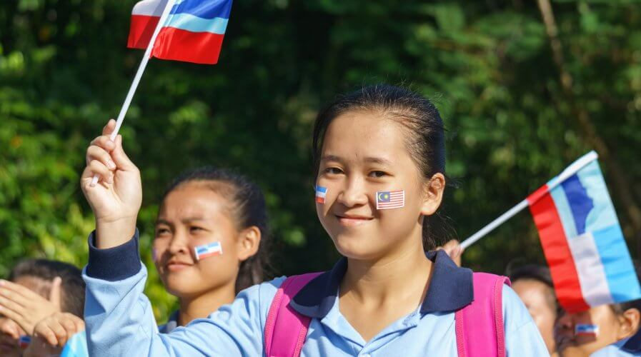 Schoolchildren waving the Sabah flag in a national day parade. Source: Shutterstock.