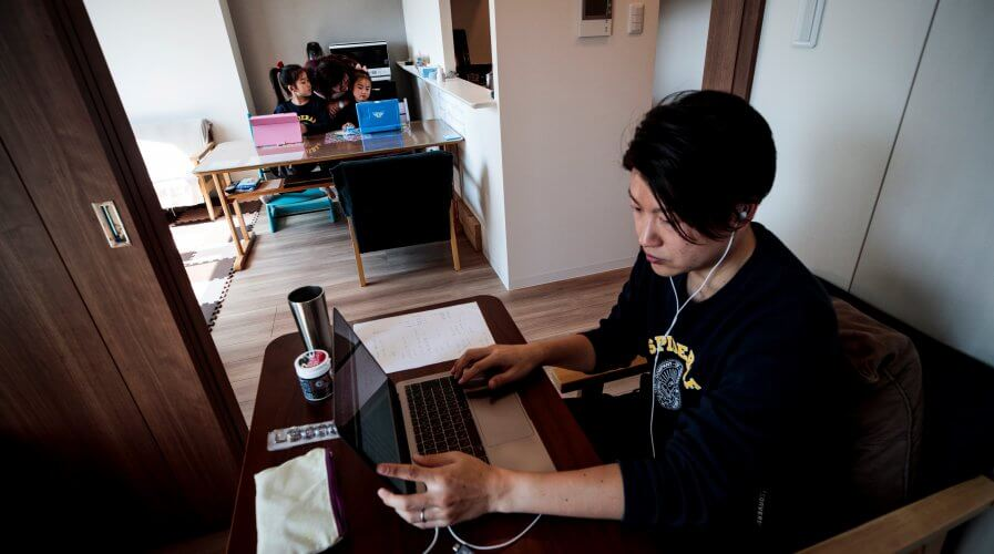 A man works from home with his wife and children in the background. Source: AFP