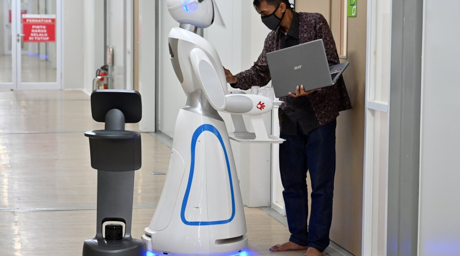 An Indonesian technician (R) examining robots known as Amy (C) and Temi (L) (black) during a simulation on assisting medical teams in handling COVID-19. Source: AFP