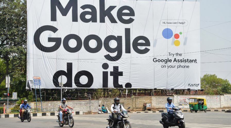 Indian commuters ride past an advertisement poster of Google in Bangalore.