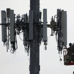 Contractors working on a cell tower to update it to handle 5G in APAC