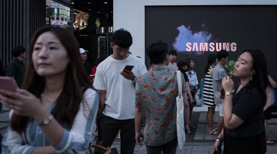 Pedestrians passing a Samsung promotional event outside a store in Seoul.