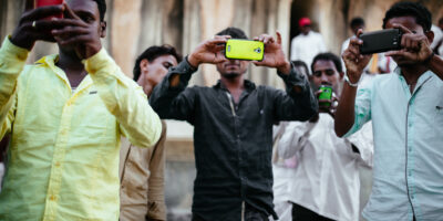 Tourists in India take pictures with smartphones.