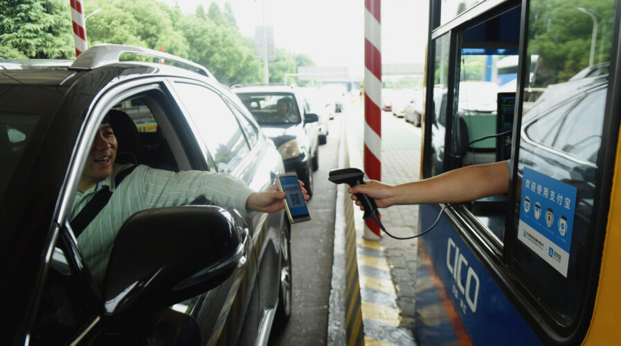 A driver uses his smartphone to pay the highway toll by way of Alipay at Pengbu toll station on the Hangzhou-Ningbo Expressway in Hangzhou