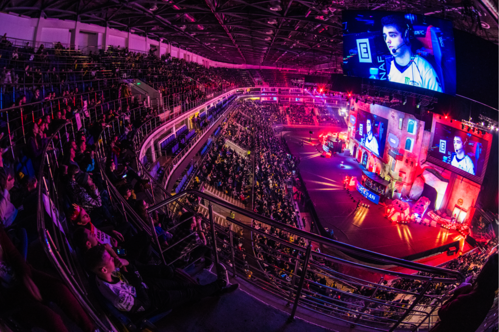 Counter Strike: Global Offensive esports event. Colorful main stage venue with lot of illumination and tribunes full of visitors and fans. Overlooking