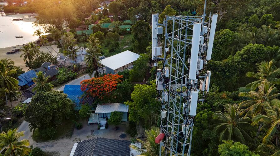 5G cell phone mast in a populated urban area. 5G tower next to houses in a town, village or city.