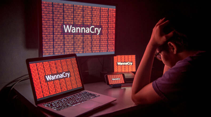 Young male frustrated, confused and headache by WannaCry ransomware attack on desktop screen, notebook and smartphone, cyber attack internet security concept