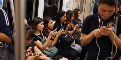 Commuters look at smartphones in Bangkok.