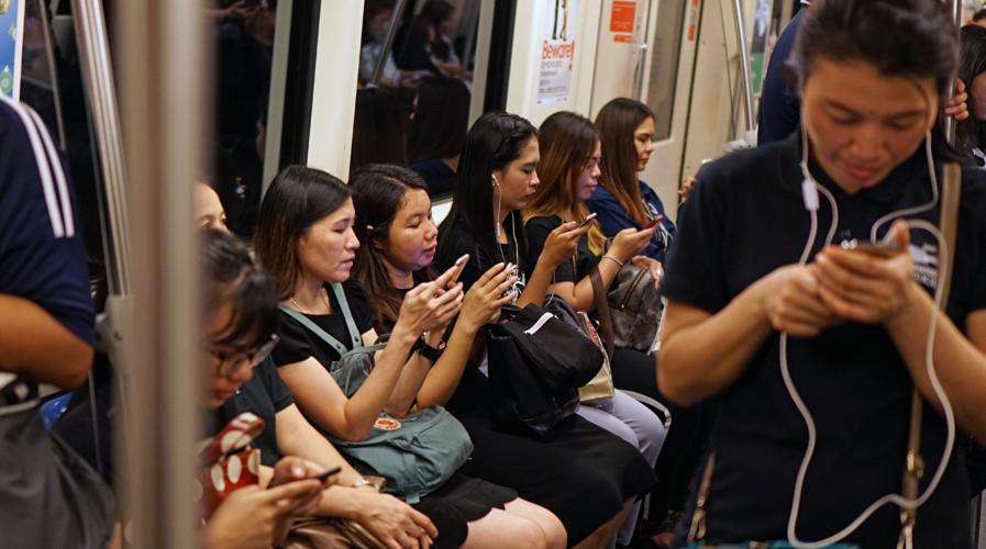 Commuters look at smartphones in Bangkok.