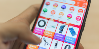 Man holding Samsung S9 with Taobao app on screen, a Chinese online shopping is a subsidiary of Alibaba Group one of the world's biggest e-commerce web