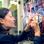 Technician fixing cable in server room