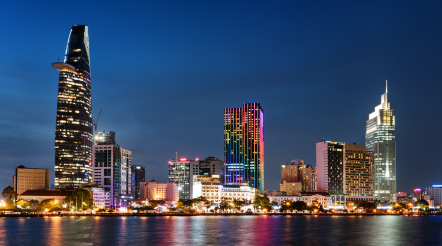 Ho Chi Minh City skyline and the Saigon River. Amazing colorful night view of skyscraper and other modern buildings at downtown. Ho Chi Minh City is a popular tourist destination of Vietnam.