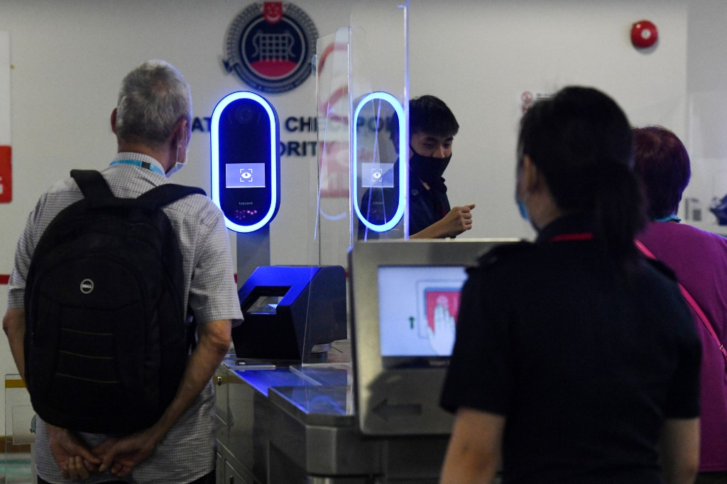 A passenger go through iris and face biometric scanning replacing fingerprint machines at the ICA Marina Bay Cruise Centre in Singapore