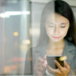 Business woman use of smart phone in city with window reflection at night