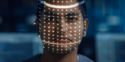 Handsome Young Indian Man is Identified by Biometric Facial Recognition Scanning Process. Futuristic Concept: Projector Identifies Individual by Illuminating Face by Dots and Scanning with Laser