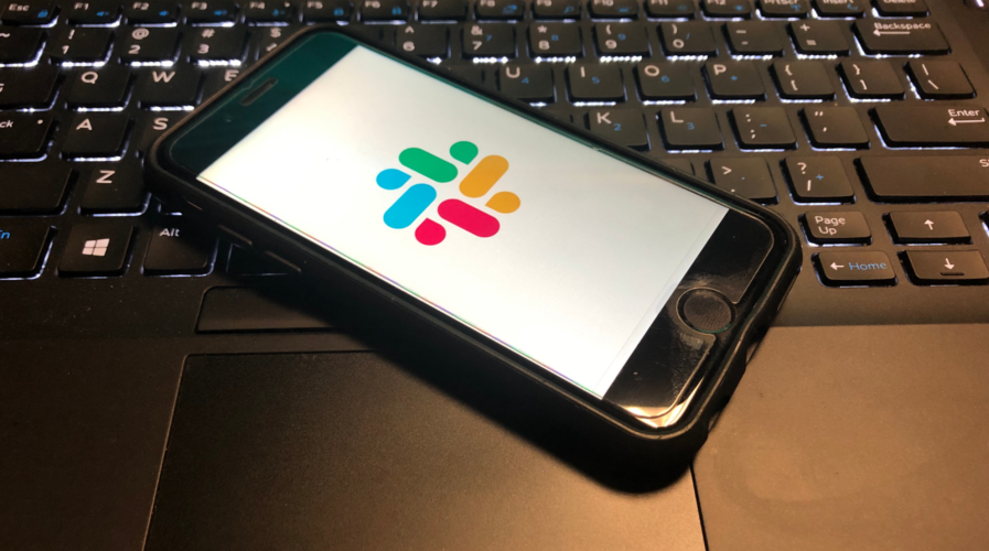 Slack App is open on a smart phone on top of a computer keyboard. Slack is a cloud based set of team collaboration software tools and online services.