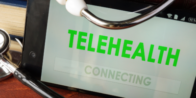 Telehealth apps open in a smartphone and stethoscope.