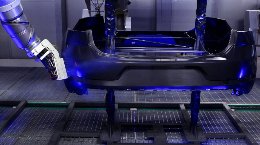 5G promises great growth for the fourth industrial revolution. An industrial robot cleans a plastic automobile bumper in a Volkswagen car factory. (Photo by RONNY HARTMANN / AFP)