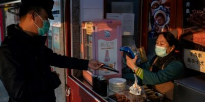 A Chinese customer makes an electronic payment on his smartphone in Beijing, China (Photo by NICOLAS ASFOURI / AFP)