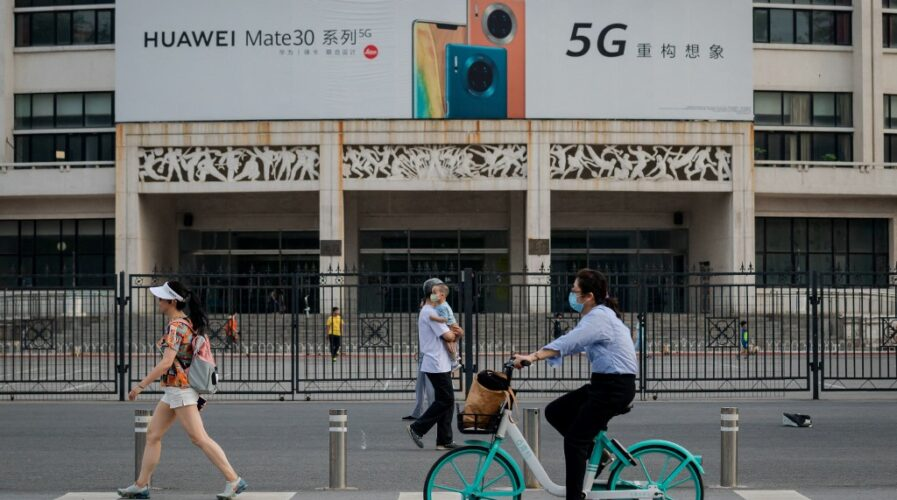 A Huawei billboard displaying their new 5G smartphone is seen in Beijing. China 5G subscriptions are projected to hit over 1B by 2026. (Photo by NICOLAS ASFOURI / AFP)