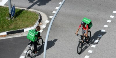 Grab delivery cyclists ride past each other in Singapore on April 20, 2020. (Photo by ROSLAN RAHMAN / AFP)