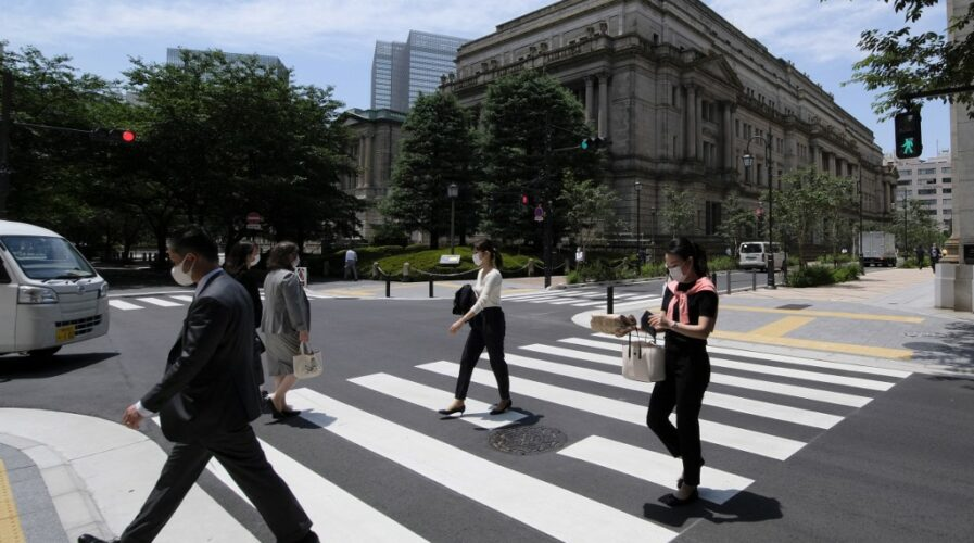 Pedestrians cross the street in front of the Bank of Japan HQ in Tokyo. The BOJ is considering issuing their own CBDC to keep up with digitalization across the region. (Photo by Kazuhiro NOGI / AFP)