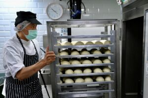 An employee from Taiwanese company Just Kitchen prepares baos for food delivery